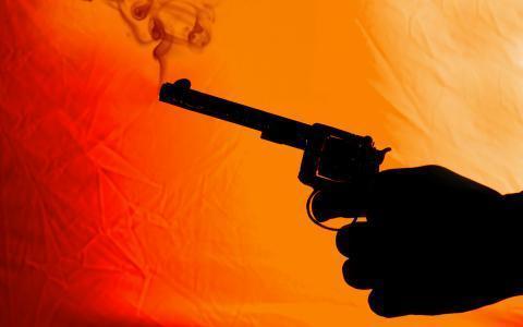 Hand holding a smoking gun