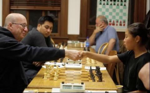 Photograph of two chess players shaking hands before the game