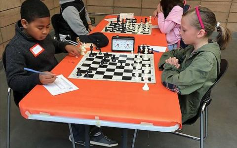 Photograph of two children playing chess